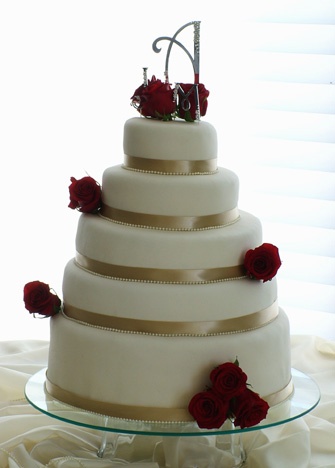 Fresh red roses and ecru satin ribbons accent this stunning wedding cake.  The cake serve 250 guests.