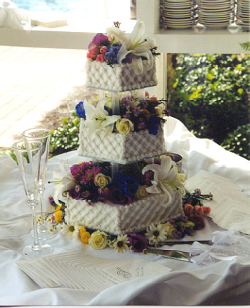 Fresh flowers adorn each tier of this buttercream covered wedding cake that has a simple lattice side design.  This cake serves 125 as pictured.
