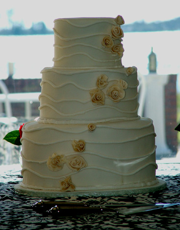Wavey lines of icing add texture to this elegant cake.  The rose buds are sugar paste.  This cake serve 230 guests.