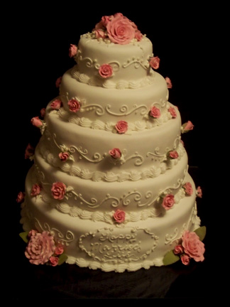 Ivory rolled fondant icing covers this 5 tiered cake.  Delicate scroll work encircles each tier along with tiny handmade sugar paste rose buds.  Full blown roses make up the topper and acent the bottom tier front and back.